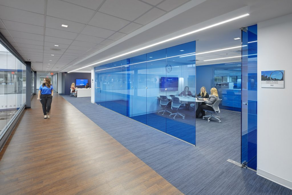 A picture of a hallway next to a conference room with blue glass walls