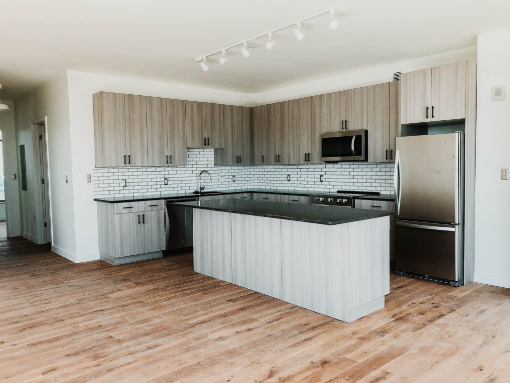 A picture of a kitchen with wooden floors in an apartment