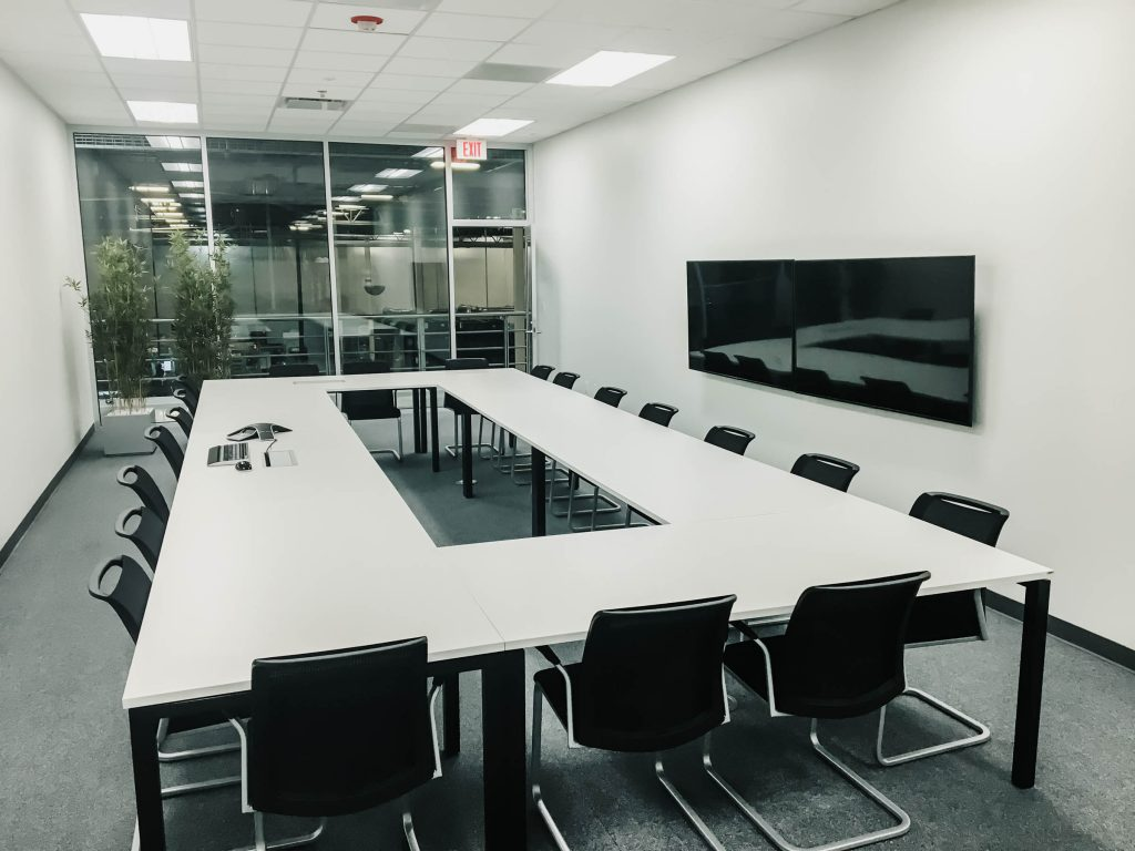 A photo of a large conference room with table, chairs and a TV.