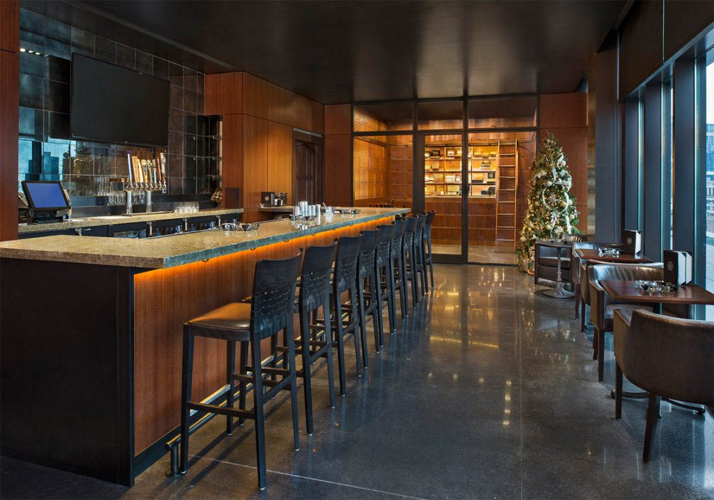 A picture of a wooded room with tables, chairs, and a bar