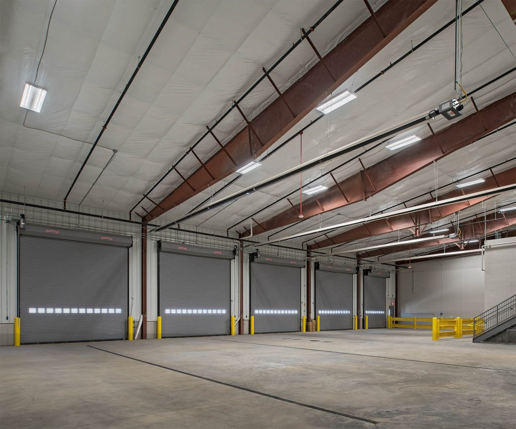 A picture of an industrial room with large doors after a design-build construction project